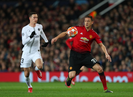 MANCHESTER, ENGLAND - FEBRUARY 12 2019: Julian Draxler of PSG and Nemanja Matic of Manchester United during the Champions League match between Manchester United and Paris Saint-Germain at Old Trafford Stadium.
