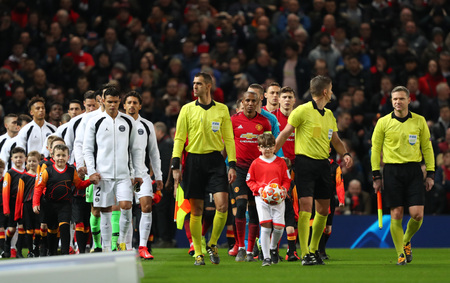 MANCHESTER, ENGLAND - FEBRUARY 12 2019: Referee leads out the teams during the Champions League match between Manchester United and Paris Saint-Germain at Old Trafford Stadium. Editorial