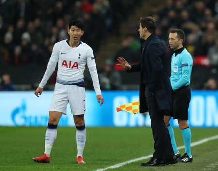 LONDON, ENGLAND - FEBRUARY 13 2019: Son Heung-Min of Tottenham gets instructions from manager Mauricio Pochettino during the Champions League match between Tottenham Hotspur and Borussia Dortmund at Wembley Stadium, London.