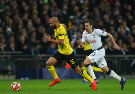 LONDON, ENGLAND - FEBRUARY 13 2019: Omer Toprak of Dortmund and Harry Winks of Tottenham chase the ball during the Champions League match between Tottenham Hotspur and Borussia Dortmund at Wembley Stadium, London.
