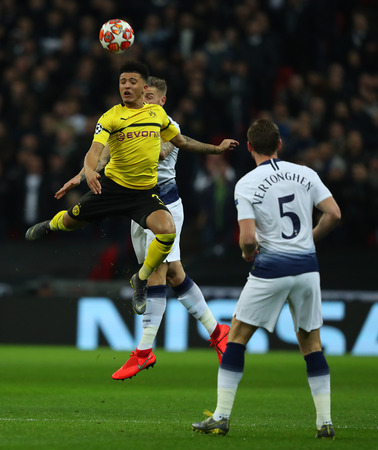 LONDON, ENGLAND - FEBRUARY 13 2019: Jadon Sancho of Dortmund and Toby Alderweireld of Tottenham compete for the ball during the Champions League match between Tottenham Hotspur and Borussia Dortmund at Wembley Stadium, London. Editorial