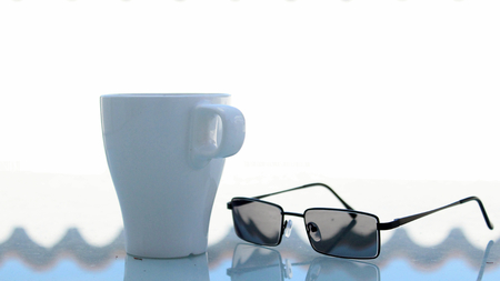 beside: White Coffee Mug Outdoors in the Morning Time with Modern Glasses Beside it. Stock Photo
