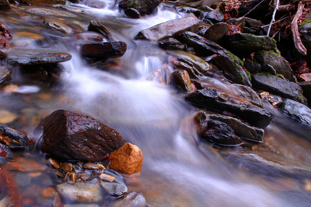 Slow Shutter Speed Photography of a Small River with Rocks in the Woods of the Mountains.