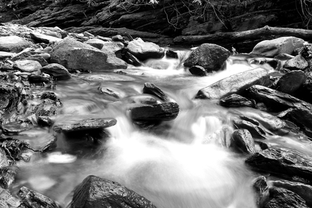 Black and White Slow Shutter Speed Photography of a Small River with Rocks in the Woods. Stock Photo