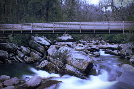 Slow Shutter Speed Photography of a Wooden Bridge over a Rushing Waterfall.