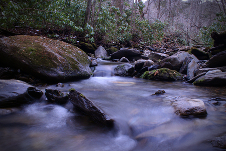 Fresh Water River with Slow Shutter Speed Photography and Rocks with Moss and Lichen. Stock Photo