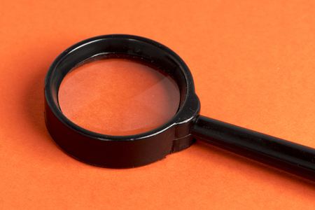 black loupe on orange background Фото со стока