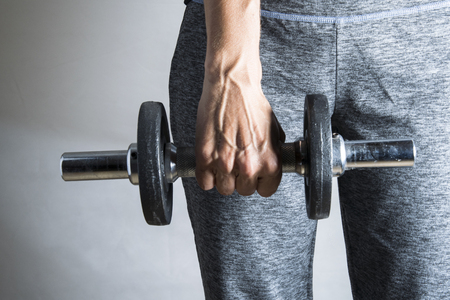 Woman holds used dumbbell in hand Stock Photo