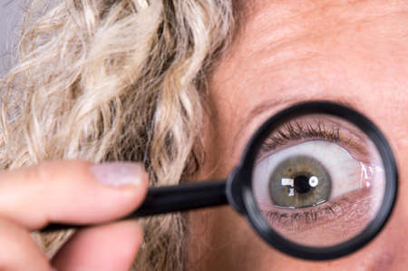 Woman looks through a magnifying glass Stock Photo