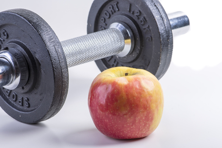 Fitness dumbbell with healthy red apple