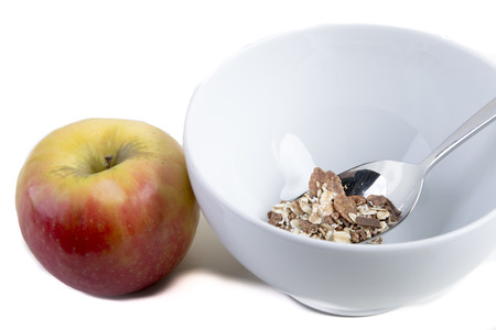 Breakfast cereals in a white bowl with a spoon and a apple