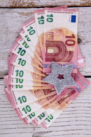 ten euro banknotes on white wood with silver star Stok Fotoğraf