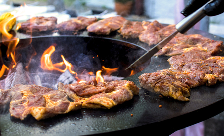 barbeque with fresh bloody steaks and open fire and the hand of a caterer