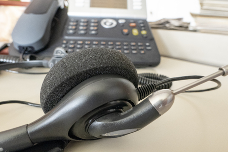 Headset with telephone in the background in the office on the desk