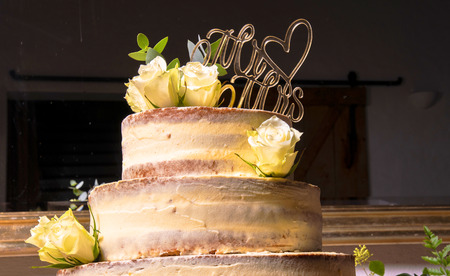 multilayer wedding cake without edge with white roses and love plugs draped against a black background 写真素材