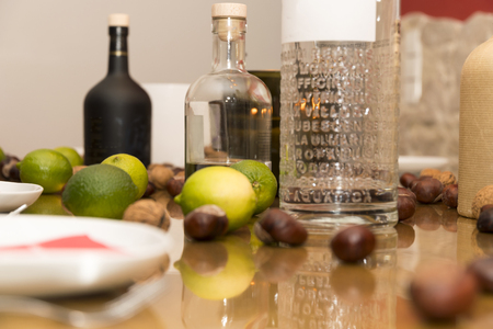 Table covered with limes and alcoholic bottles of schnapps and gin before a party