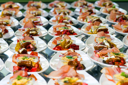 Caterer puts the starter on many plates with vegetables and antipasti
