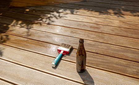 empty beer bottle and a brush are lying on the half recessed terrace with glaze 스톡 콘텐츠