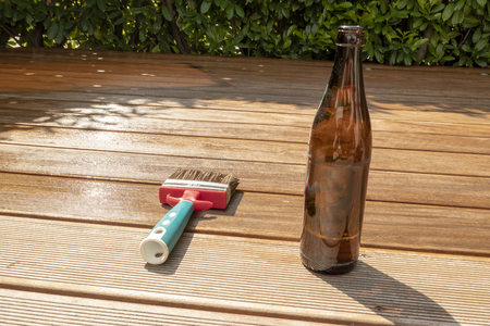empty beer bottle and a brush are lying on the half recessed terrace with glaze Banco de Imagens