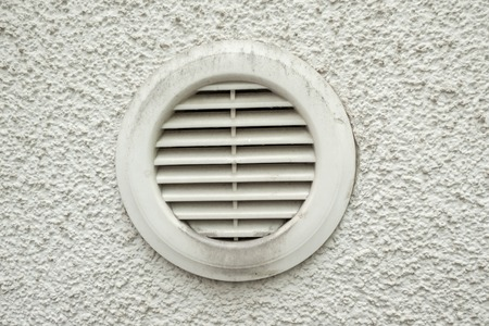 Plastic ventilation outlet on a house wall with air slits and dirt