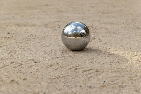 silver shiny boules ball in the sand