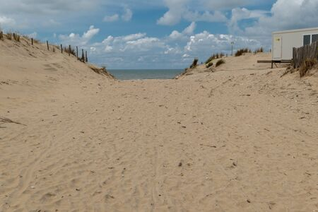 Dune with passage to the Atlantic Ocean and cloudy sky