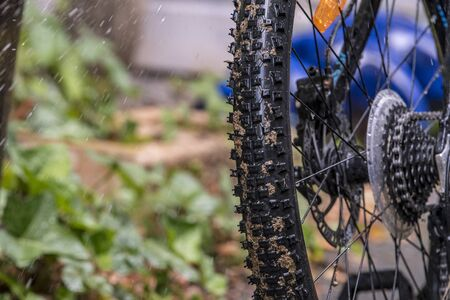 Child repairs and cleans his bike with water