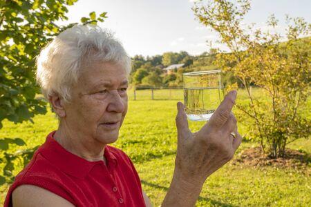Senior citizen enjoys testing a glass of water in the garden