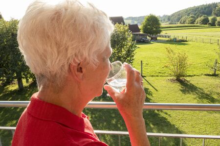 Senior citizen drinking a glass of water in the sun in the garden
