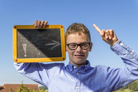 Calculations on the blackboard with arrow on the head of a boy with glasses