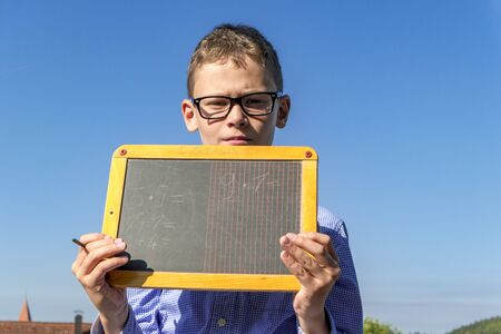 Boy with arithmetic problems on a blackboard with glasses in front of a blue sky Stock Photo