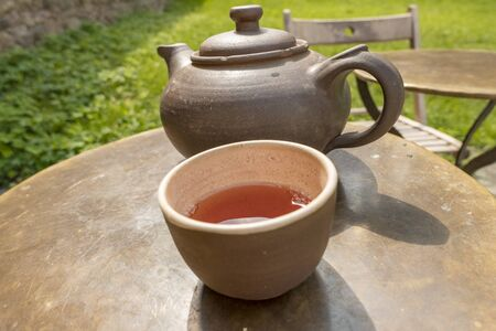old clay teacup and teapot on steel table
