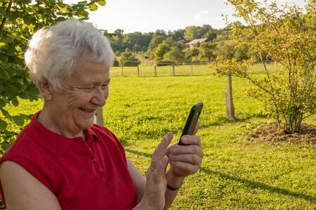 laughing senior lady looks astonished at your mobile phone and checks her messages