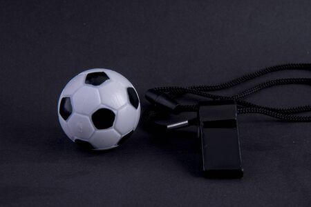 whistle with football on black background