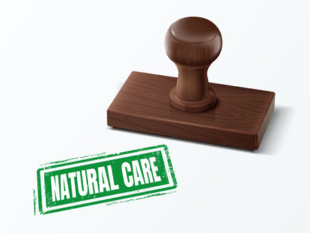 Natural care green text with dark brown wooden stamp.