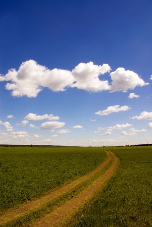 Cloudy sky and the earth road trough the meadow Stock Photo
