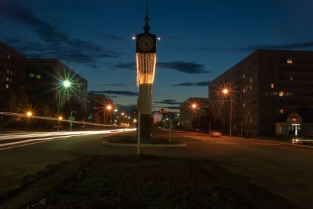 Night street with clock and glowing lamps Stock Photo