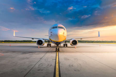 Modern commercial airplane in the parking lot of the airport apron, waiting for services maintenance, refilling fuel, and passenger boarding the plane. Concept of travel, holidays and business jet