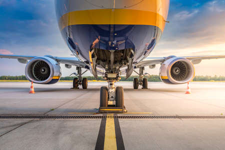 Closeup on airplane landing gear in the parking lot of the airport apron, waiting for services maintenance, refilling fuel services. Concept of aircraft enginering, technology, holidays and travel Stock fotó