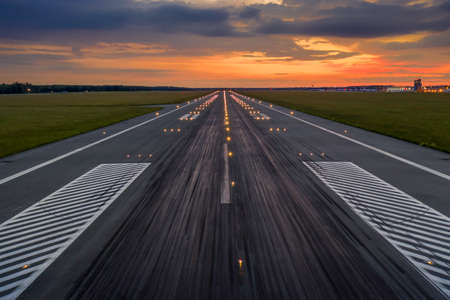 Used concrete asphalt airport empty runway with many braking marks, markings for landings and all navigation lights on. Clear for comercial airplane landing or taking off in Wroclaw airport