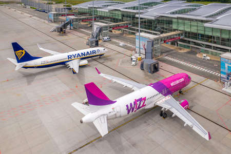 Wroclaw, Poland - June 17, 2020: Airbus and Boeing in front of Wroclaw Airport waiting for maintenance. Jet bridges and airport equipment around. Aerial airplanes photo taken from the drone Sajtókép