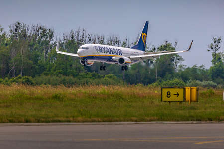 Wroclaw, Poland - June 17, 2020: Airplane Boeing 737-800 on aproach to land, just before touch down. Armed landing gear is ready. Aircraft side seen from the taxiway in Wroclaw Airport