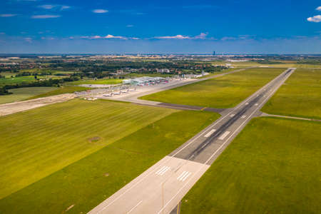 Wroclaw, Poland - June 17, 2020: EPWR Wroclaw Airport terminal, airport apron and runway at 11 approach seen from bird eye view. Photo of aerodrome taken from drone Sajtókép