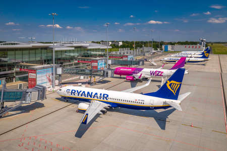 Wroclaw, Poland - June 17, 2020: Ryanair Boeing and WizzAir Airbus airplanes parked in front of Wroclaw Airport waiting for maintenance and services. Aerial airplanes photo taken from the drone Sajtókép