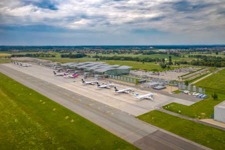 Wroclaw, Poland - June 17, 2020: Ryanair, Wizz Air and Enter Air airplanes parked in front of Wroclaw Airport terminal waiting for maintenance and services. Aerial airplanes photo taken from the drone