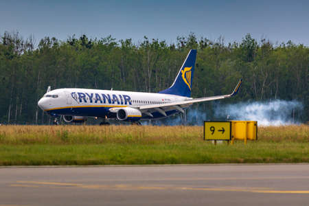 Wroclaw, Poland - June 17, 2020: Ryanair airplane aproached the runway and touched down. Hard braking and tire burning against tarmac for quick high speed reduce at Copernicus Wroclaw Airport