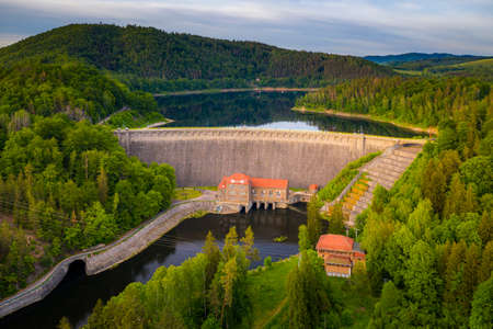 Water turbines are producing clean electricity at power plant in Pilchowice power plant. River dam and mountains. Drone shot of stone dam at reservoir, hydroelectricity power station
