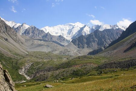 Snowy mountains with glacier with blue sky. Kazakhstan, Tian-shan