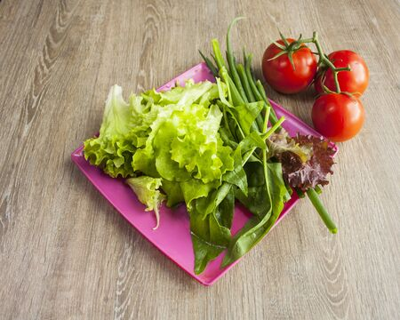 Salad with greens, cherry tomatoes, onions on pink square plate with wood background, close up view