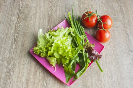 Salad with greens, cherry tomatoes, onions on pink square plate with wood background, overhead view